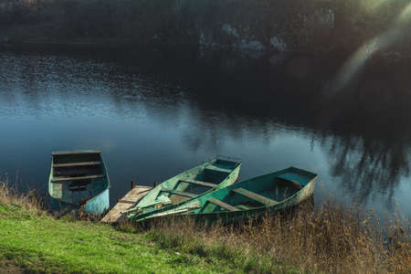 Three wooden boats peacefully resting on an autumn river at the sunset