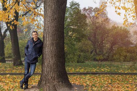 Handsome man walking in the autumn park