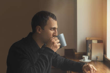 Young man in casual clothes drinks coffee while sitting in a cafe. Man drink coffee in cafe. Cozy atmosphere. Coloring and processing photo. Stock Photo