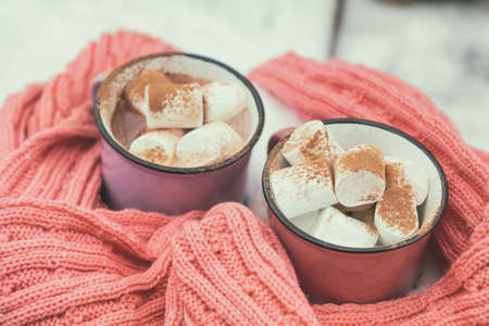 Hot chocolate with marshmallow in pink and violet two cups wrapped in a cozy winter pink scarf on the snow-covered table in the garden. Coloring and processing photo small depth of field Stock Photo