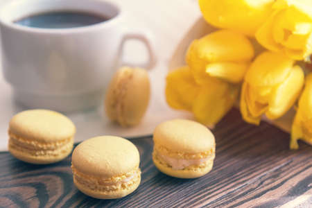 Beautiful spring music background. Cup of coffee, macaroons, yellow tulips, musical page on a dark wooden background.