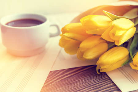Beautiful spring music background. Cup of coffee, yellow tulips, musical page on a dark wooden background. Stock Photo