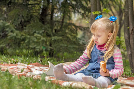 Cute little blonde girl with two ponytails relaxing with a book and a bun in the city park on a spring sunny day. Stock Photo