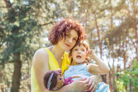 Young mother and little daughter playing in the park on a summer sunny day Stock Photo
