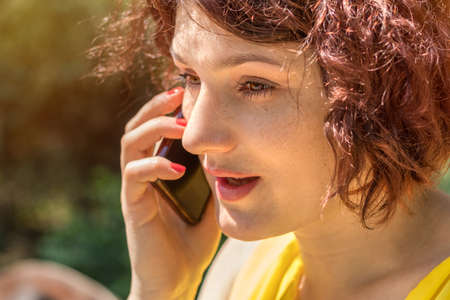 Young redhead woman talking on the phone outdoors on a sunny day.  Portrait redhead woman on the phone with copy space Stock Photo