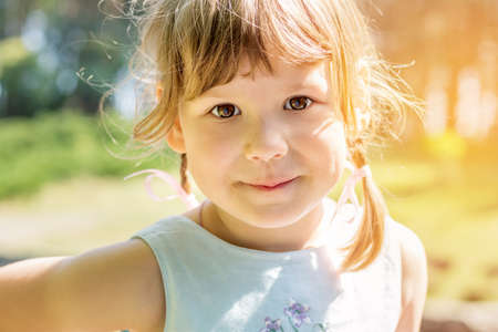 Cute little girl plaing in the city park on a summer sunny day. Portrait little girl close up, big brown eyes.
