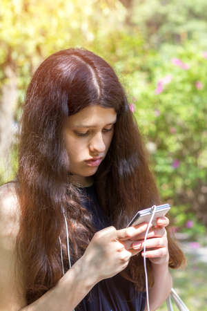 Young long haired girl using the phone in the city park on a summer sunny day. Walking in summer park on the summer day. Portrait female  teenager.