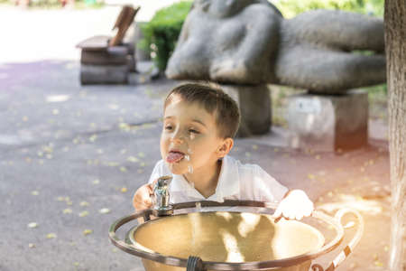 Happy little boy drinking water from fountain in the city park on a summer sunny day. Close up. Beautiful summer background with copy space Stock Photo - 92942796