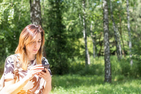 Young redhead woman using the phone outdoors on a sunny day.  Portrait redhead woman on the phone with copy space Stock Photo - 92953523