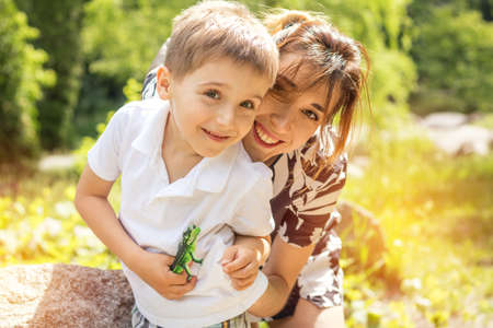 Happy little boy playing with his mother in the city park on a summer sunny day. Mother and son in the park near pond. Stock Photo - 92929616