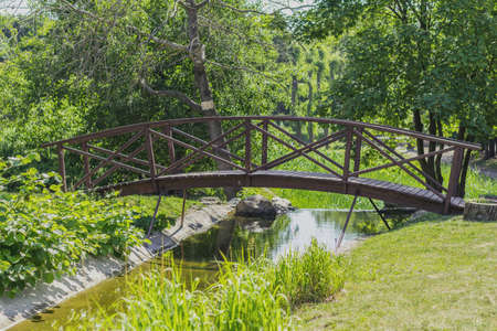 Summer footpath in the city park with a bridge on a sunny day Stock Photo