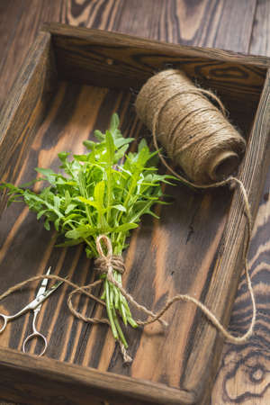 Top view of the bunch of fresh arugula in a wooden box. Dark wooden background. Toned photo. Shallow depth of the field. Stock Photo - 93130845