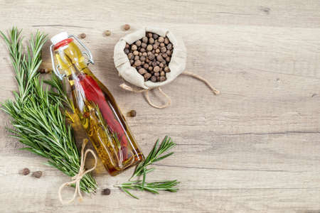 Rosemary bunch of bouquets, olive oil with pepper and spices, fragrant pepper on light wooden surface. Top view, copy space. Stock Photo