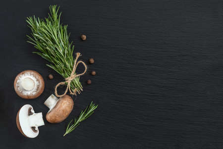 Rosemary bunch of bouquets, mushrooms and fragrant pepper on black stone surface. Top view, copy space. Stock Photo