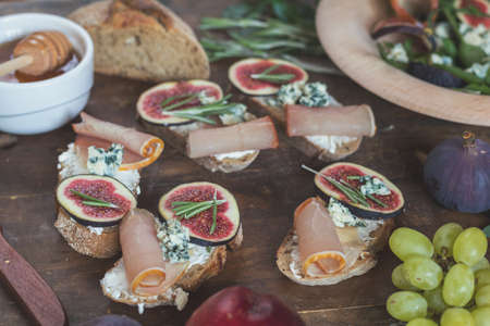 Easy diet salad with arugula, figs and blue cheese on a brown wooden surface. Sandwiches with ricotta, fresh figs, prosciutto, rosemary and blue cheese. Delicious fruity breakfast, top view. Toned.