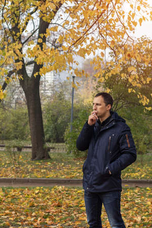 Handsome man walking in the autumn park. Man smoking cigarette in outdoor.