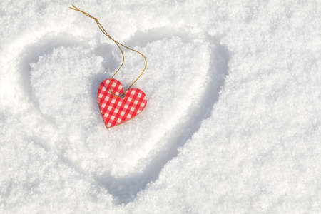 Beautiful valentine holiday background with checkered motley heart on white snow surface. Stock Photo