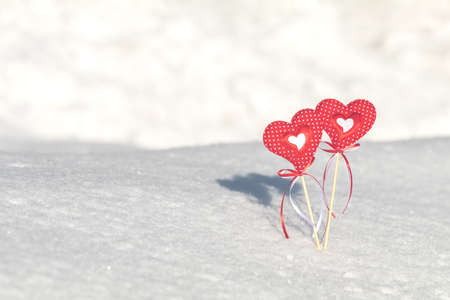 Beautiful valentine holiday background with two checkered hearts on cane, white snow surface.