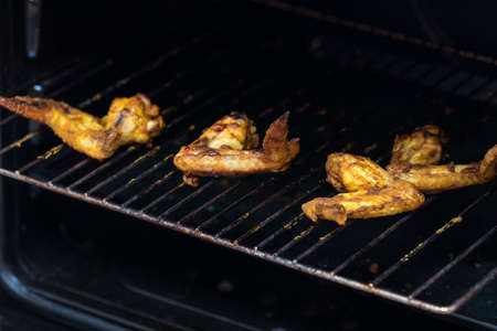 Roasted chicken wings on grill in the oven. Fresh grilled chicken meat. Dark background, shallow depth of field. Stock Photo