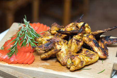 Grilled chicken wings on a light oak surface.  Stock Photo