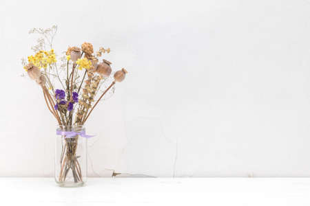 Composition of dried flowers and herbs, poppy heads in a glass jar with violet ribbon. White wooden surface close to the white cracked wall. Light tones, copy space Stock Photo - 95631874