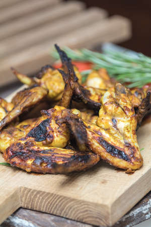 Pile of roasted grilled chicken wings on oak wooden board. Fresh vegetables and greens on the background. Fresh grilled chicken meat. Shallow depth of field. Stock Photo