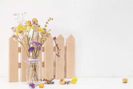 Dried flowers and poppy heads on a stem in a glass jar. Wooden decoration. White wooden table, white cracked wall. Light tones, copy space.
