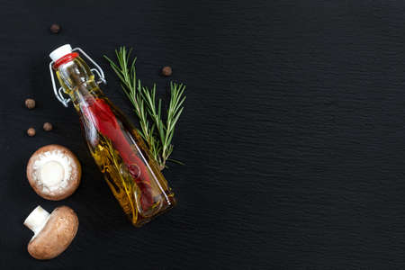 Rosemary bunch, mushrooms, olive oil with pepper and spices and fragrant pepper on black stone surface. Top view, copy space. Stock Photo - 96083062