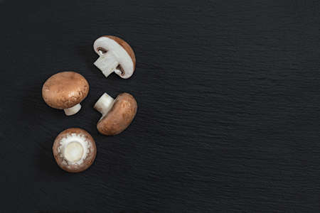 Mushrooms on black stone surface. Top view, copy space. Fresh raw champignon with a brown cap on dark background. Stock Photo - 96098729