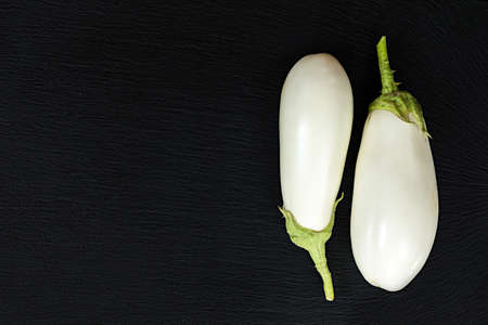 White eggplant on a black stone surface. Top view. Copy space. Stock Photo - 96609595