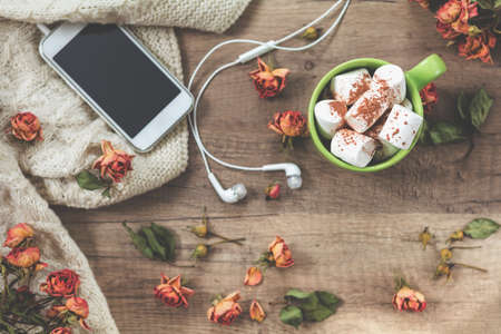 Cup of coffee with marshmallow, white knitting wool, dried roses flowers, mobile phone and headphones. Beautiful romantic female's background. Shallow depth of field, marshmallow in the focus