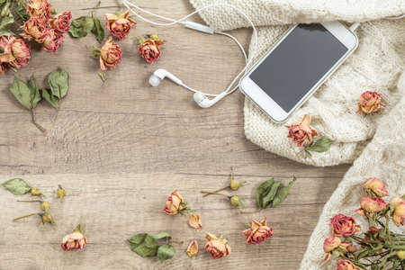 White knitting wool, dried roses flowers, mobile phone and headphones. Beautiаul romantic female's background.