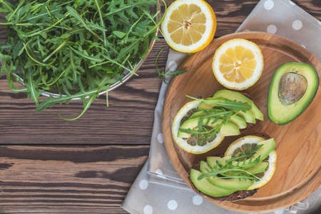 Rye bread with cut avocado, arugula and lemon on round board. Healthy delicious nutritious breakfast on wooden table, top view, copy space.