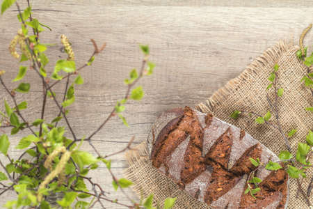 Birch tree blossom branch and rye bread on the wooden background with copy space, toned photo Stock Photo - 100550380