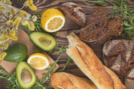 Healthy delicious nutritious ingredients for breakfast. Rye bread, baguette, avocado and lemon, fresh arugula. Dark wooden table, top view, copy space.