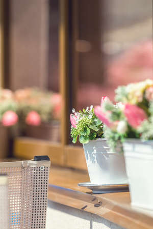 Street cafe flowers and herbs decor concept. Many beautiful flowers in the pot at the cafe. Sunny day. Shallow depth of field.