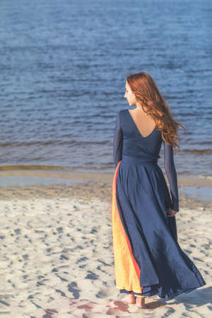 Beautiful cute pretty redhead female teenager in long romantic dark blue dress barefoot at the river in the sunny evening. Stock Photo - 101104809