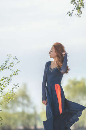 Beautiful cute pretty redhead female teenager in long romantic dark blue dress at the river in the sunny evening. Stock Photo - 101118128
