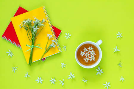 Cup of tea with white flowers on bright green surface. Many blossom flower heads ornithogalum and red and yellow notebooks with bouquet near.