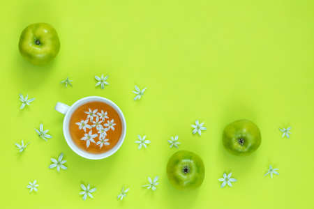 Cup of tea with white flowers on bright green surface. Many blossom flower heads ornithogalum and green apples near.