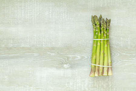 Beautiful food art background. Asparagus sprouts on light wooden surface. Stock fotó