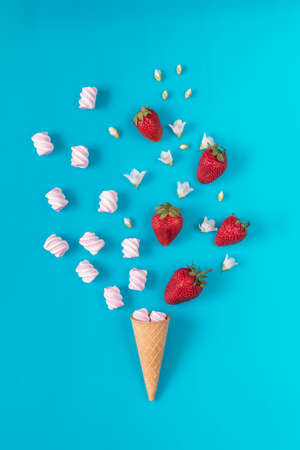 Waffle cone with marshmallows, fresh strawberries and flowers jasmine blossom bouquets on blue surface. Flat lay, top view sweet food floral background. Stock Photo