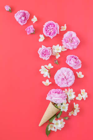 Waffle cone with pink roses and jasmine flower bouquet on pink background. Flat lay, top view floral background.