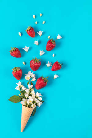 Cup of tea with fresh strawberries and flowers jasmine blossom bouquets on blue surface. Flat lay, top view sweet food floral background.