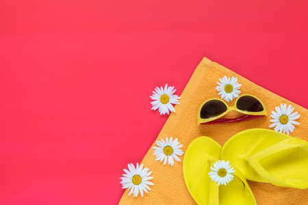 Summer yellow accessories with chamomile flowers on pink floor. Top view and copy space, picturesque. Mock up and fashion and beauty. Stock Photo