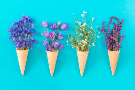 Four waffle cones with thyme, cornflower, blue bells and white flowers blossom bouquets on blue surface. Flat lay, top view floral background.