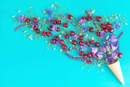 Waffle cone with red cherries, cornflower, blue bells and white flowers blossom bouquets on blue surface. Flat lay, top view sweet food floral background. Stock Photo