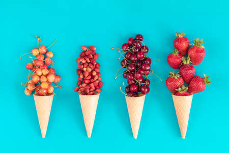 Four waffle cones with red cherries, wild strawberries, yellow cherries, and strawberryes on blue surface. Flat lay, top view sweet food background. Stock Photo