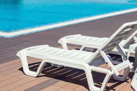Swimming pool with wooden deck at hotel.Summer sunny day. Lounge chairs, beach sunbeds in a swimming pool invite you to relax Stock Photo