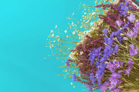 Thyme, cornflower, blue bells and white flowers blossom bouquets on blue surface. Flat lay, top view floral background. Stock Photo - 102826673